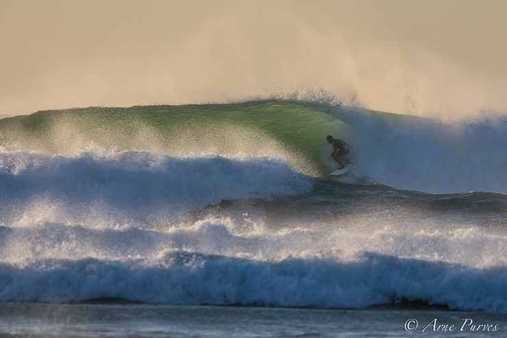 A backlit surfer tucks into a cold Atlantic barrel at Dunes, Noordhoek beach